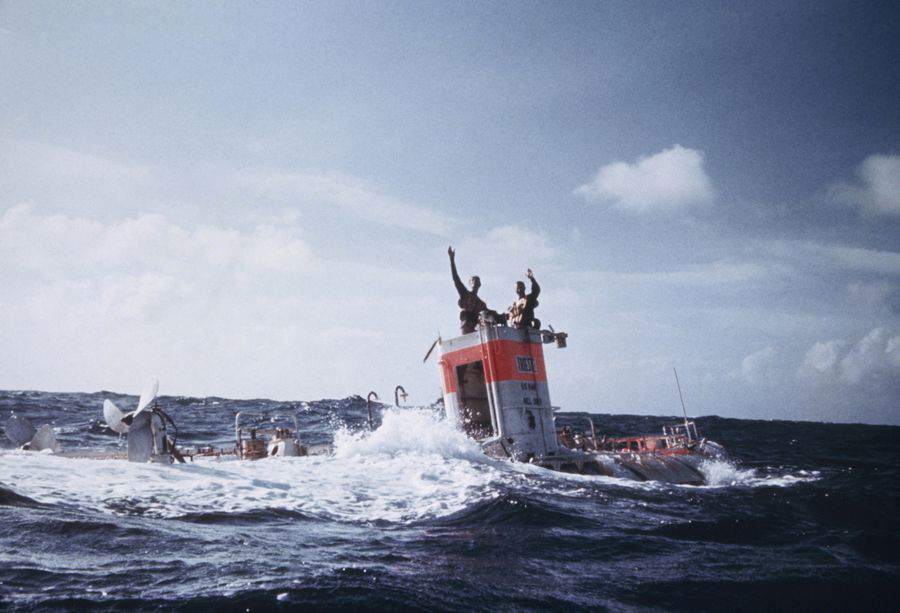Jacques Piccard and Don Walsh emerge from the bathyscaphe Trieste following their successful descent to the bottom of the Pacific Ocean's Mariana Trench in January 1960. Walsh and Piccard were the first people to reach the trench's ? and Earth's ? lowest point, Challenger Deep, some 35,800 feet below the ocean surface. Piccard, who died in 2008, was posthumously awarded the Hubbard Medal, the National Geographic highest honor, at a ceremony in Washington, D.C., on June 14, 2012 (Photo: Thomas J. Abercrombie; ? National Geographic)