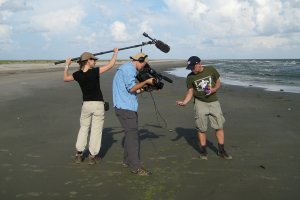 Ocean Doctor president Dr. David E. Guggenheim with PBS NewsHour crew holding a tar ball from BP Gulf oil spill